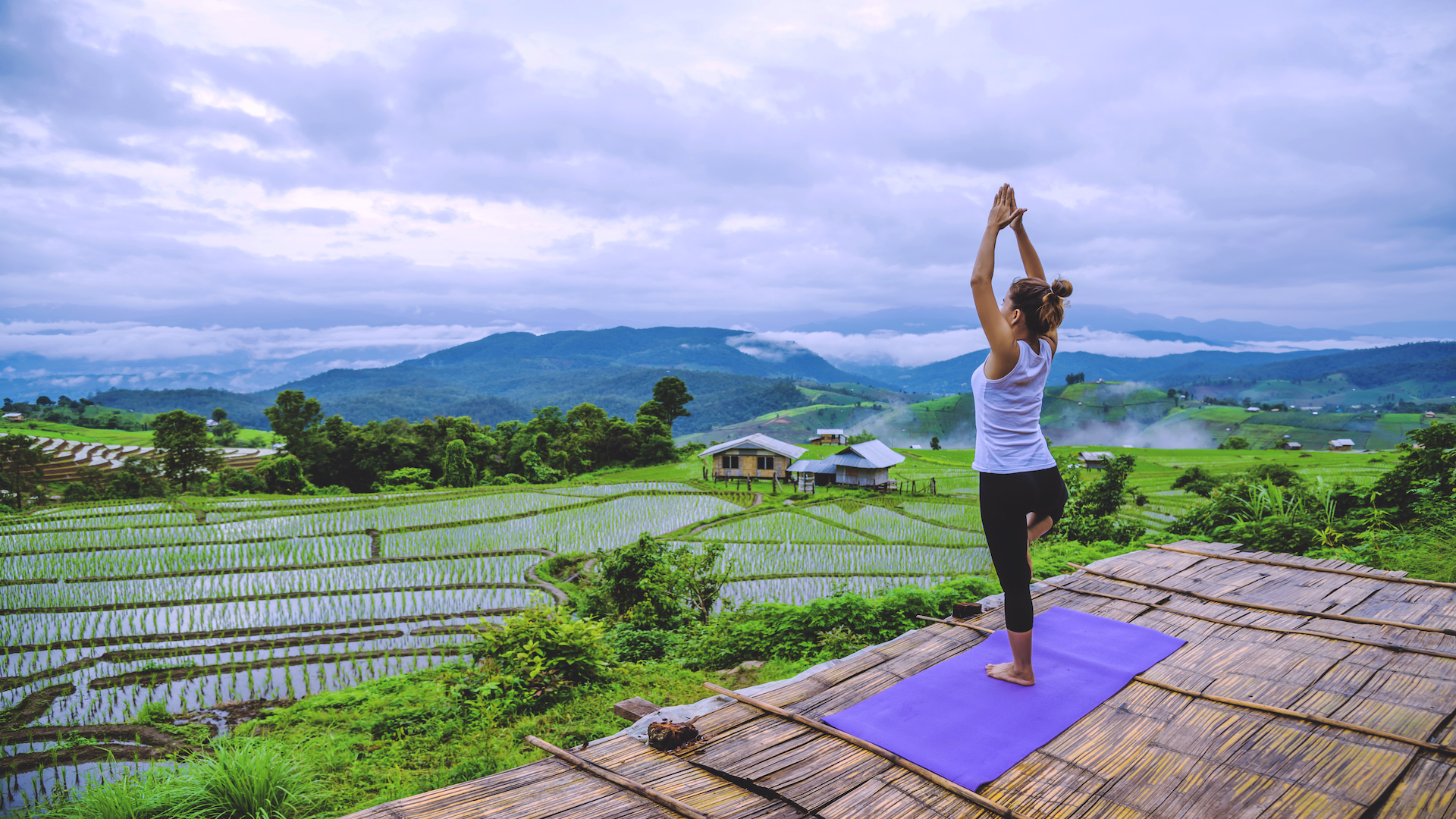 Woman doing yoga in front of rice fields
